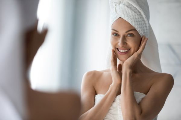 Woman with towel on head admires her face
